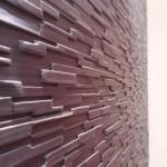 Szczegół drewnianego panelu imitującego elewację z kamienia